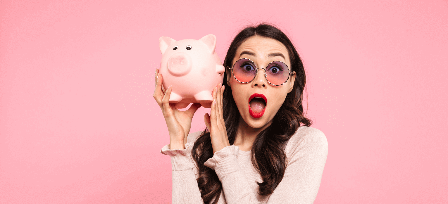 Girl wearing sunglasses and a sweater holding a pink piggy bank