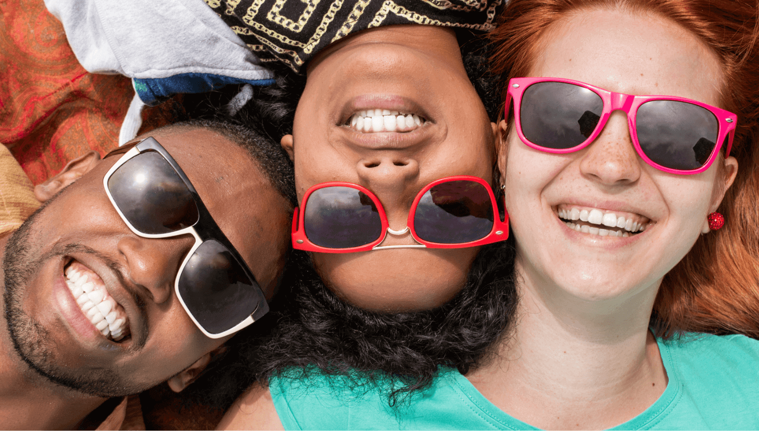 Multicultural friends wearing pink and orange sunglasses lying down
