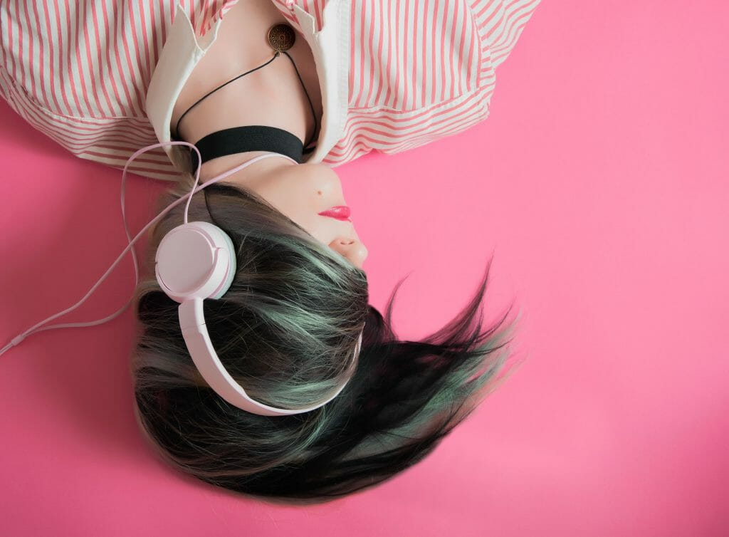 woman listening to music through headphones while thinking of payday loans no credit check instant approval