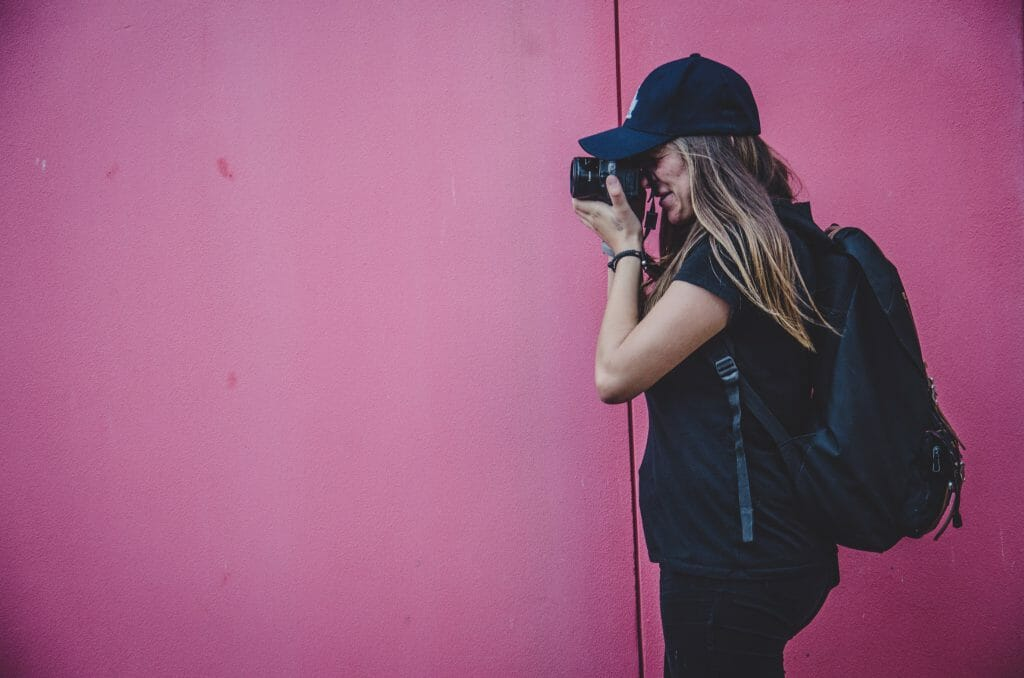 woman in baseball cap using camera bought with online loans
