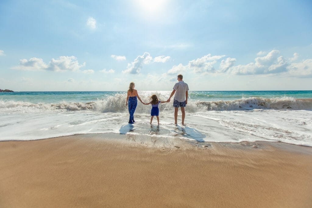 Family splashing in the ocean and enjoying holiday loans