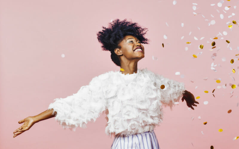 woman dancing in confetti after being approved for loans