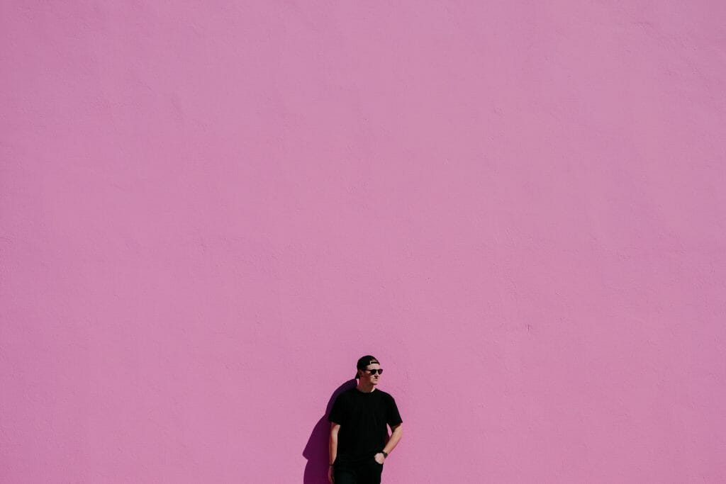 Man standing against pink wall thinking about no paperwork loans