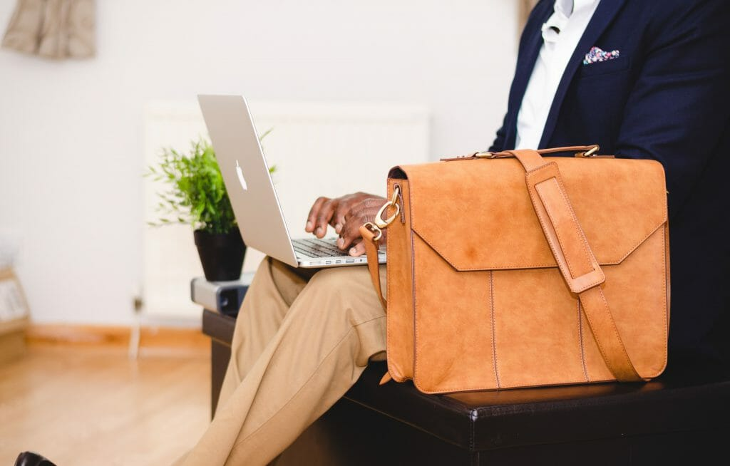 Man sitting down with brown satchel browsing for fast approval loans on laptop
