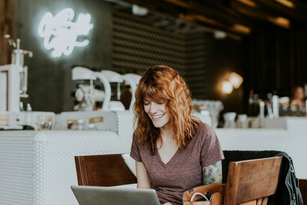 Woman in cafe browsing for fast money loans on laptop