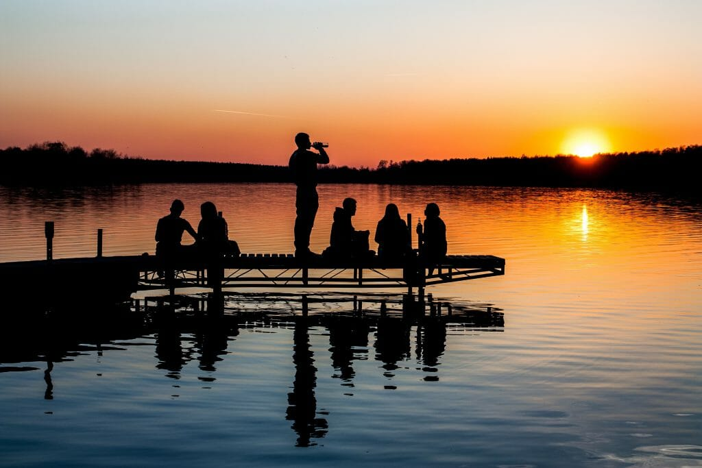 People sitting on jetty at sunset with payday loans weekend payout