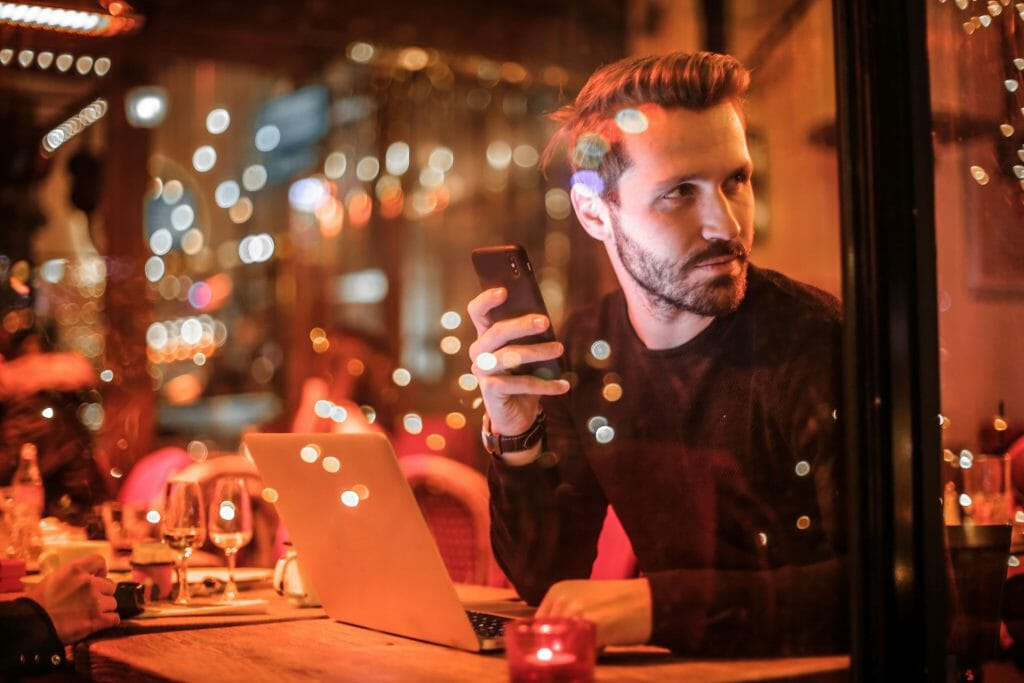 Man in cafe at night time applying for 24/7 payday loans