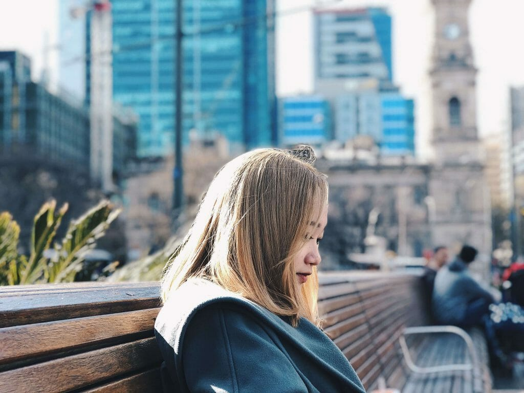 Woman sitting on bench looking at cash loans Adelaide