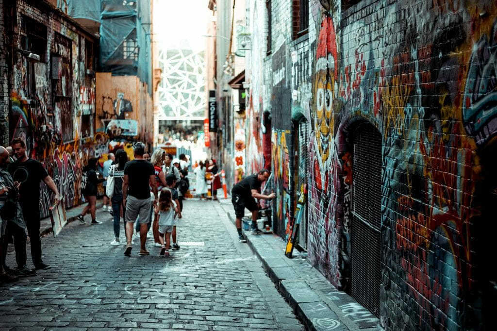 People in alleyway with graffiti saying cash loans Victoria