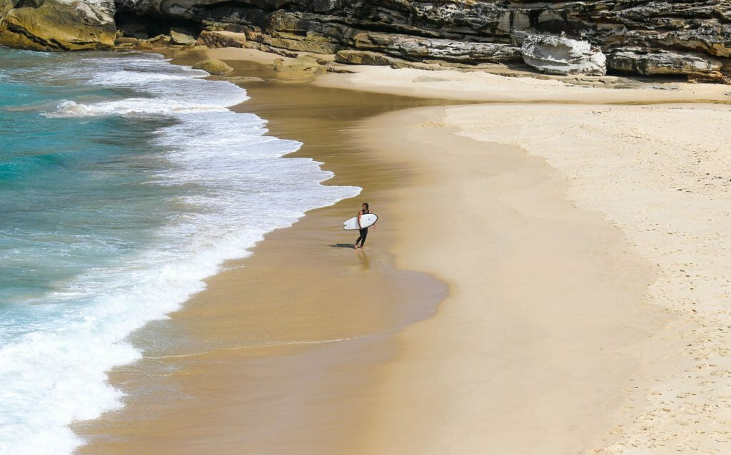 Man walking with surfboard on beach walking towards payday loans Centrelink